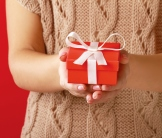 Two hands holding red gift box with white ribbon