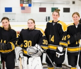 Image of four female hockey players on ice