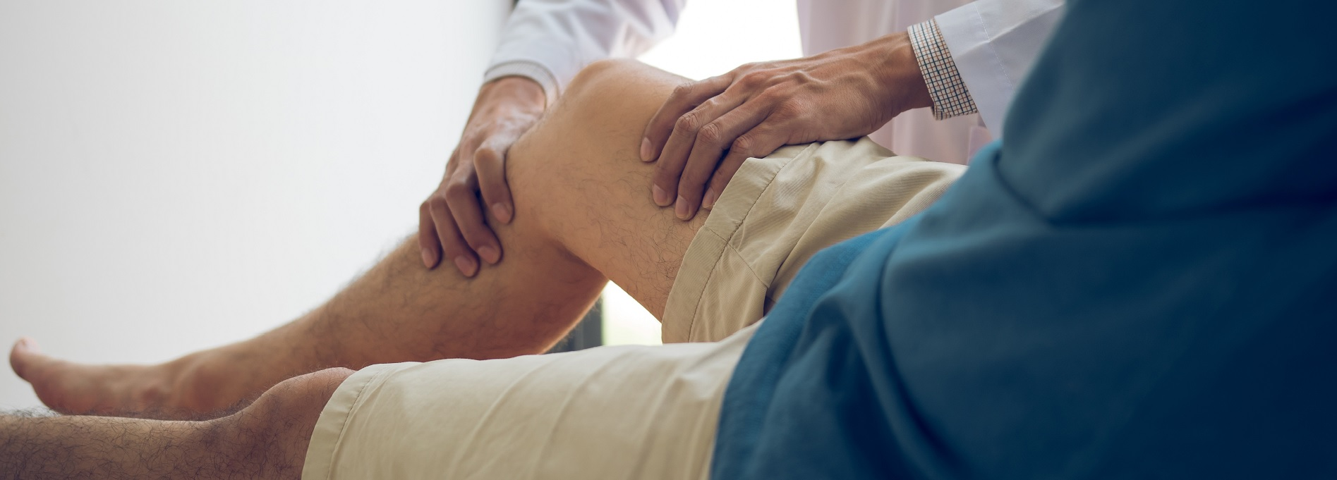 Orthopedic provider examining patient's knee